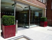 city-college-entrance-pair-of-red-cubico-planters-with-topiary-box-squares